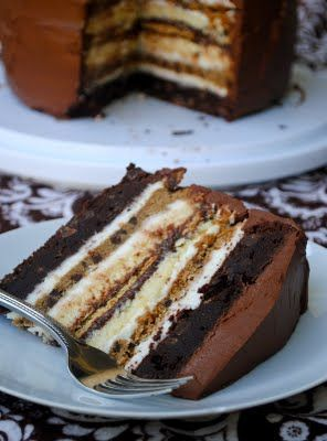 The Ultimate S'mores Anniversary Cake with:    2 brownie layers  2 cheesecake layers  2 chocolate chip cookie layers  5 graham crackers  marshmallow frosting  and chocolate frosting!