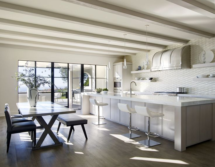 Kitchen features an oversized island lit with @JonathanBrowning pendants. All seating surfaces are covered with faux leather for easy cleanup after the kids, naturally.   #odginteriors #modern #mediterranean #kitchen