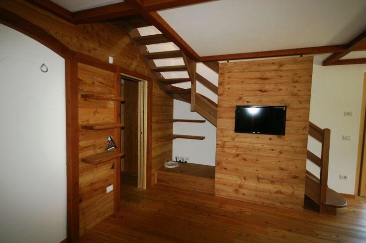 """Ambiente soggiorno con pannello parete """"isola"""" con inserita Tv , cassettone e rivestimento pareti e soffitto. Realizzazione con larice antico recuperato da vecchi e dismessi """"masi"""" e fienili."""