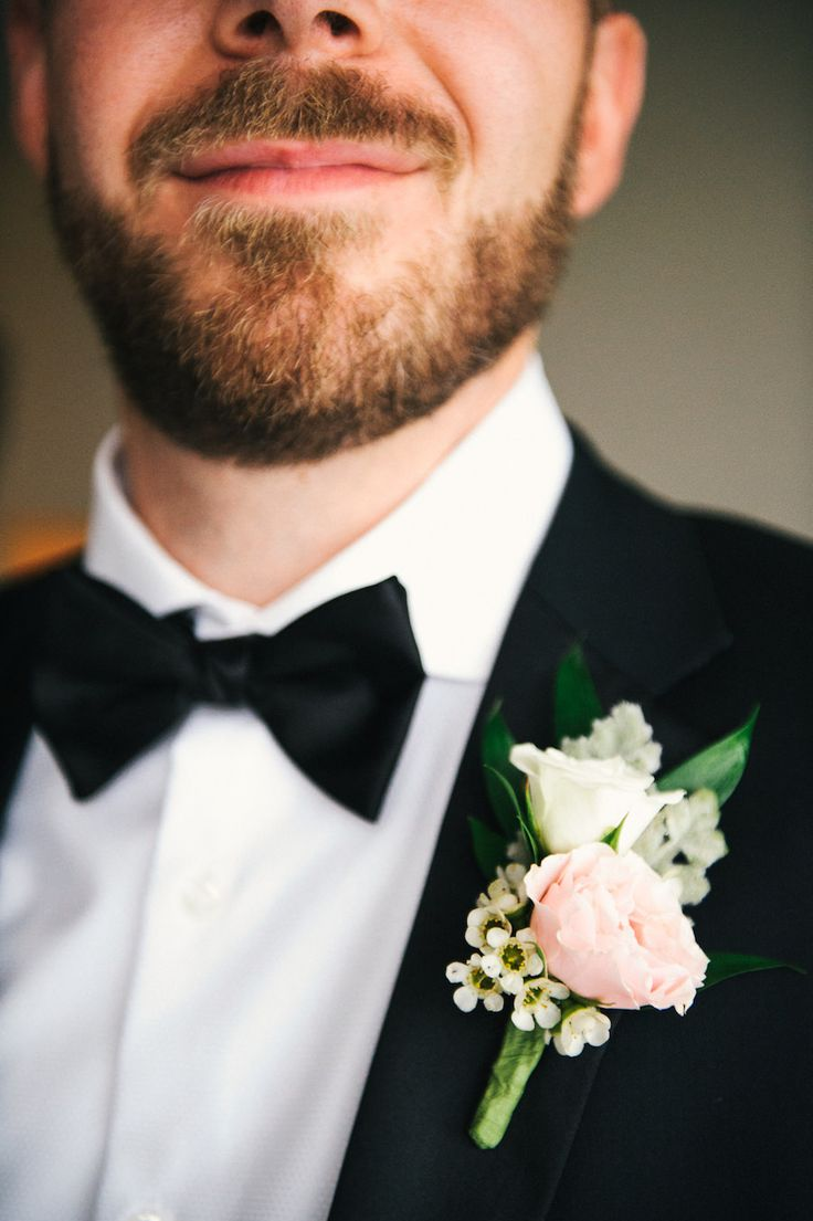 Groom In Black Tuxedo With Bowtie Wearing Blush Pink And Ivory Wedding Boutonniere