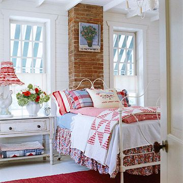 """Cottage Style Layered Bedding:   In a cottage guest room, a painted iron bed is piled high with red, white, and blue linens. The homeowners layered a floral dust ruffle, cornflower blue and white sheets, and red gingham comforter with a vintage quilt and plaid and striped pillow cases. An embroidered """"Home Sweet Home"""" pillow tops off the look."""