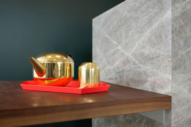 Brass Tom Dixon tea set on a coral Hay Kaleido Tray sit against a deep green background | Haven (373 Dominion Road, Auckland) | Photo by the talented Jeremy Toth | Fit out by Material Creative.