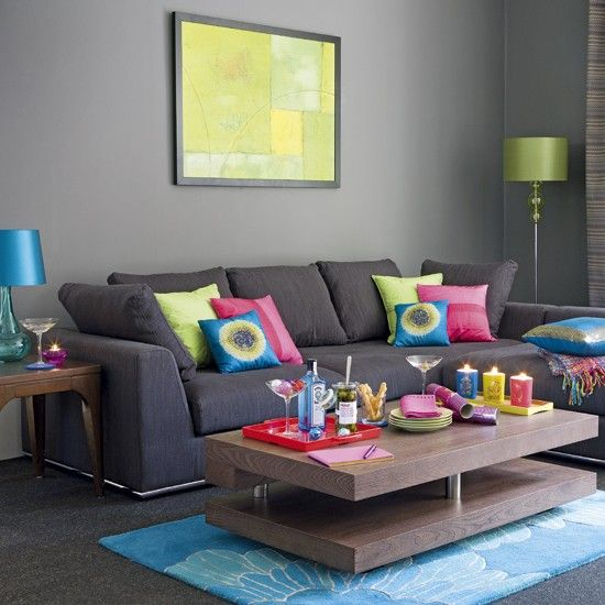 Grey walls and flooring, with a charcoal sofa, set a sophisticated to this living room while colourful accessories add a vibe