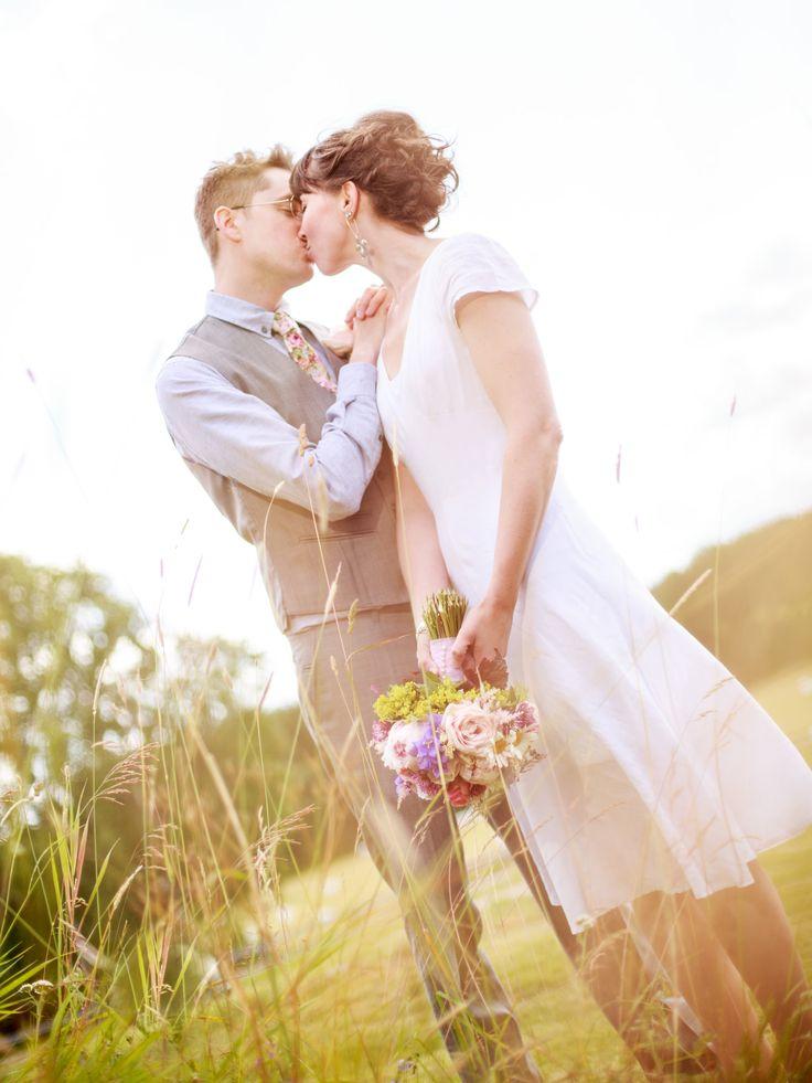 Brudpar på äng, kyss, bröllop