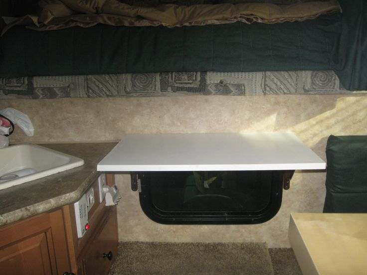 they placed a drop leaf shelf over the window between the cab of the truck and the camper.  when its down it protects the window while climbing in bed, when its up, its used for extra counter space - great idea