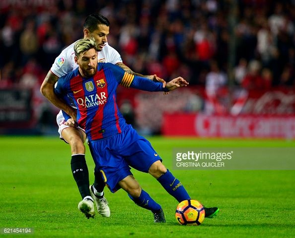 Barcelona's Argentinian forward Lionel Messi vies with Sevilla's midfielder Vitoloduring the Spanish league football match Sevilla FC vs FC Barcelona...