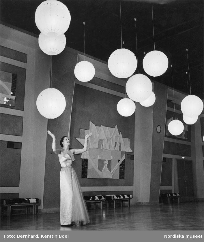 Kvinna i hellång aftonklänning och aftonhandskar i stor lokal med rislampor i taket. Foto: Kerstin Bernhard, 1950