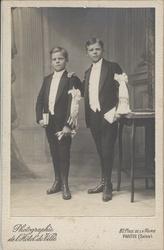 Maurice en Achile Vanhecke poseren voor de fotograaf ter gelegenheid van hun Plechtige Communie. Zij waren tijdens de Eerste Wereldoorlog samen met hun ouders en zuster gevlucht uit Brielen, eerst naar Reningelst en vandaar naar Pantin in Frankrijk (departement Seine). De foto is genomen in 1918.