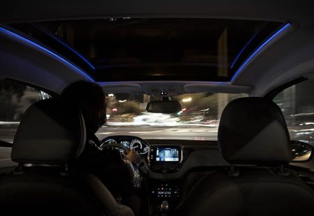 Peugeot 208 med blå lysdioder som lyser upp panoramaglastaktets kanter i mörker.