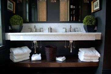 Dark contemporary bathroom featuring white marble slab vanity with dark stained wood shelving beneath.