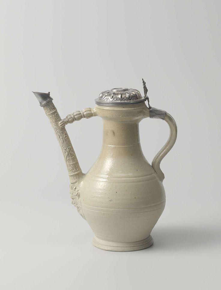 Anonymous | Spouted jug, Anonymous, c. 1580 | Tuitkan van steengoed. Het peervormige lichaam is zwak horizontaal geribd. De brug naar de tuit heeft de vorm van een arm. Onder de tuit een gekroond baardmasker (?). Met een zilveren, geornamenteerd deksel. In het midden een wapen en op de rand een inscriptie: OOSTDICK.