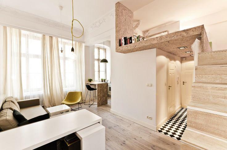 """Quarto no mezanino - O apartamento com 29 m² na Polônia, era mais alto do que amplo: com pé-direito de 3,7 m, o jeito foi elevar o dormitório para um semi-mezanino, 1,85 m acima de um corredor com banheiro e guarda-roupas. A ideia também possibilitou a integração das áreas de uso diurno e convívio social - estar, jantar e cozinha - no """"pavimento principal"""". O projeto de interiores é do escritório polonês 3XA."""