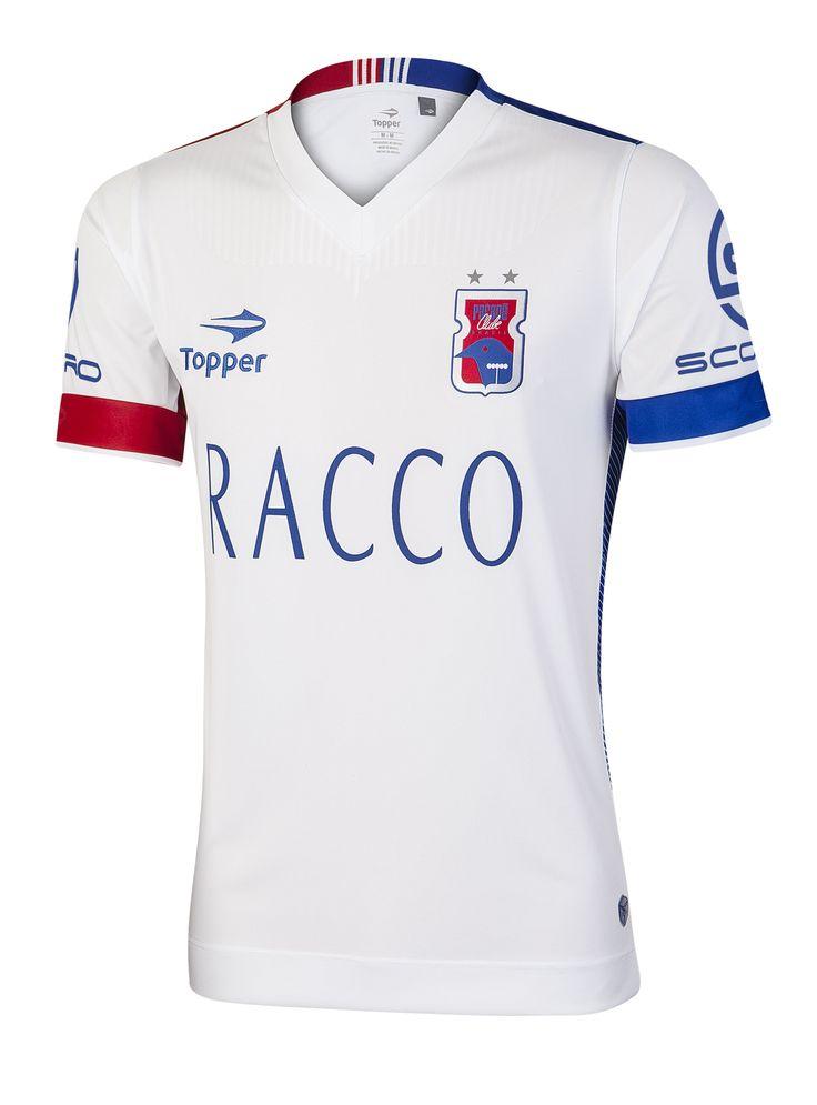 """O segundo uniforme do Paraná é inspirado no pinhão: abaixo da gola em """"V"""" há um grande desenho que remete à semente. Com a cor predominante em branco, a camisa conta com detalhes em azul e vermelho."""