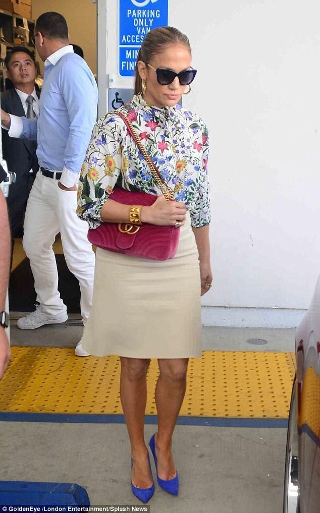 Jennifer Lopez wearing Gucci Gg Marmont Velvet Bag, Thierry Lasry Sexxxy Sunglasses in 384 Blue, Gucci Flora Print Shirt, Hermes Collier De Chien Cuff and Gucci Wool and Silk-Blend Skirt