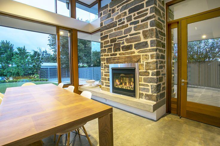 Gas fireplace, stone clad, feature concrete shelving & polished concrete flooring