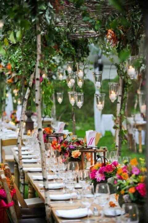 Diese zauberhafte und farbenfrohe Tischdekoration mit vielen bunten Blumen und hängenden Kerzen ist eine tolle Idee für ein Freiluftfest.
