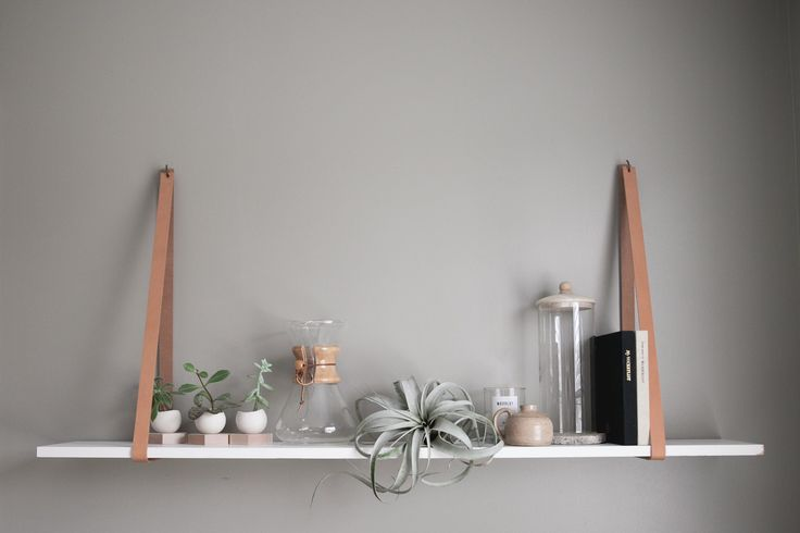 A simple DIY leather shelf, made from two straps and a shelf left behind in the home's closet.