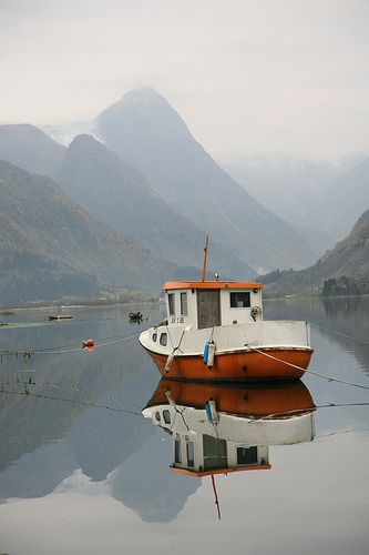 This is a small fishing boat in the Fjærland fjord in Norway. The Jostedalen glacier in the background. A fantastic place!
