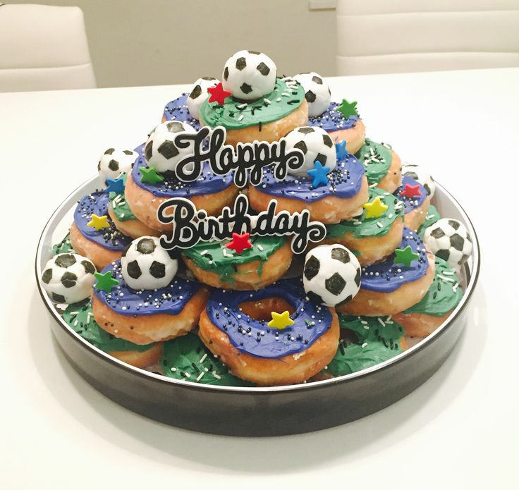 Soccer donut birthday cake⚽️!! Very simple and fun to make. Just spread icing over some plain donuts and add sprinkles To make the mini soccer balls, wrap white fondant around donut balls, and draw the black pentagons with an edible marker.