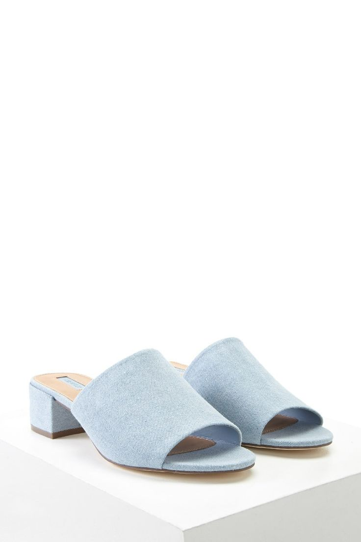 A pair of mules crafted from denim with an open toe and a block heel.