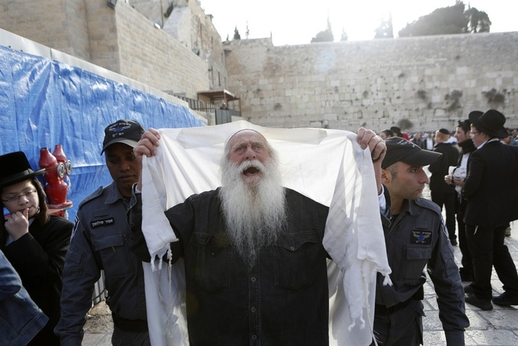 Police officers detain an ultra-Orthodox Jewish man at the Western Wall on April 11, 2013, after he burned a book belonging to the Women of the Wall, a group opposed to police-enforced Orthodox controls at the Jerusalem holy site.