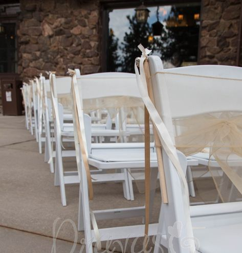 Chairs dressed up with organza bows and a ribbon wedding wand with bells.