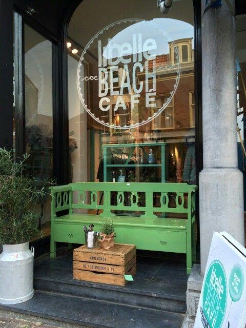 Groene oude brocante klepbank van WWW.OLD-BASICS.NL bij Libelle Beach Café in Haarlem. Old BASICS: webshop en grote winkel vol unieke oude brocante, landelijke, industriële en vintage meubels.