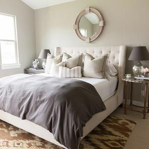 Alice Lane Home - bedrooms - mirror over headboard, white and gray bedding, dark gray duvet, cream tufted headboard, ivory and brown Ikat rug, round studded bedside tables, mercury glass lamps, mismatched nightstands