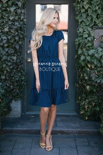 You can never go wrong with an adorable polka dot dress! Navy dress has ruffle details along the neck and hemline, an elastic waist, and back keyhole closure.