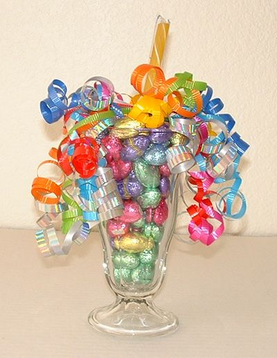To make this Easter treat you will need: a Sundae glass, Easter candy (Hershey's chocolate kisses, Easter chocolate eggs, or jelly beans in Easter colors), a stick candy, curling ribbons in Easter colors, pipe cleaners or thin stem wire, scissors and wire cutters. I think this would be a cute centerpiece for a kids table or gifts to the kids on Easter