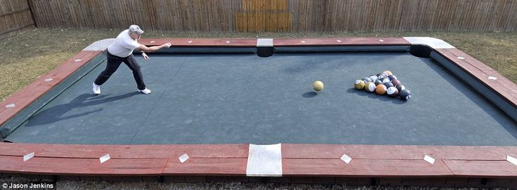 Rack & roll: Steve Wienecke throws a ten-pound bowling ball he uses as a cue-ball on the giant pool table he built in his back garden in Missouri. Pool table 30ft long, 1-1/2 ft high, felt covered. He wants to develop portable tables for bars with large gardens. Interesting. kn