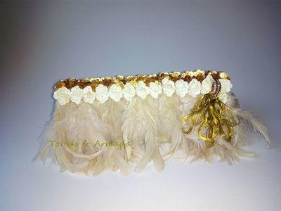 Bolso de fiesta con plumas y lentejuelas . Tonos marfil y dorados .