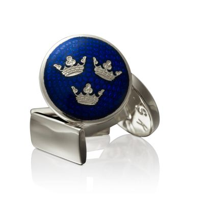 SKULTUNA  TRE KRONOR  €60  Cufflinks from Skultuna adorned with the Swedish kingdom emblems. They are made of silver plated brass and the subject has a blue background.
