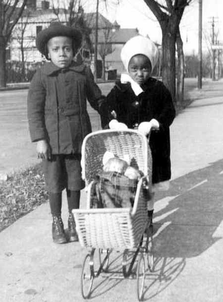 boy and a girl with a doll pram