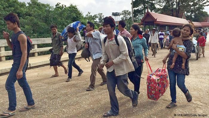 Cambodian migrant workers walk across the Cambodia-Thailand border in Cambodia's western Battambang province on June 15, 2014. More than 110,000 Cambodians have fled Thailand to return home in the past week, an official said on June 15, amid fears of a crackdown on migrant workers after last month's military takeover.