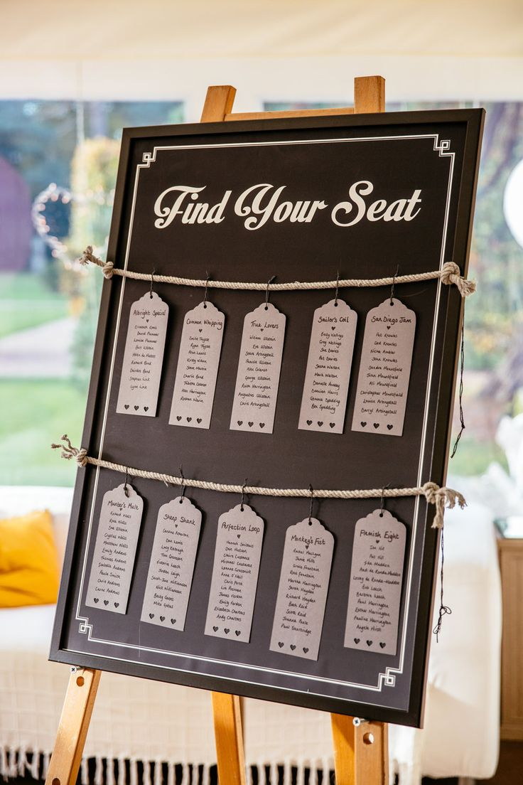 Blackboard table plan with luggage tag tables tied to rope - Image by Cassandra Lane Photography - Raimon Bundo wedding dress for a classic wedding in Iscoyd Park with grey bridesmaid dresses, morning suits and bright florals.