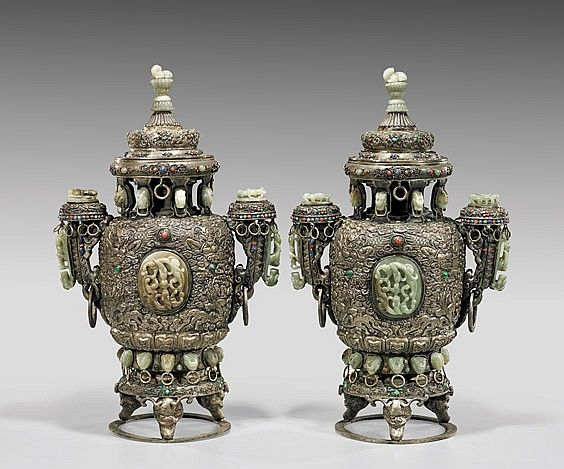 """PAIR LARGE CHINESE JADE-SET REPOUSSÉ URNS each body with design of fabulous creatures amid swirling clouds in relief, with a large oval double-chilong jade plaque to either side, the spire-like covers each surmounted with a sectional carved jade animal finial; each urn """"jeweled"""" with coral-glass, turquoise, malachite and lapis lazuli pieces; and each with approx. 27 inset celadon jades; all set upon three fantastical heads on a ring mount; H: 21 3/4"""" (each approx.)"""