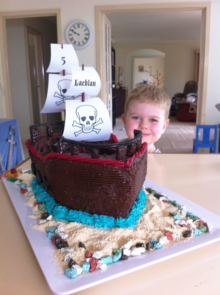 Pirate ship cake with biscuit crumb sand and chocolate candy rocks