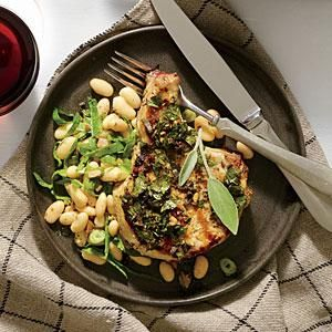These grilled chops rest in and absorb an herb vinaigrette for a few minutes while you mix what might be the easiest side dish ever--a toss of white beans, briny green olives, and fresh spinach that matches up beautifully with the juicy pork chops.