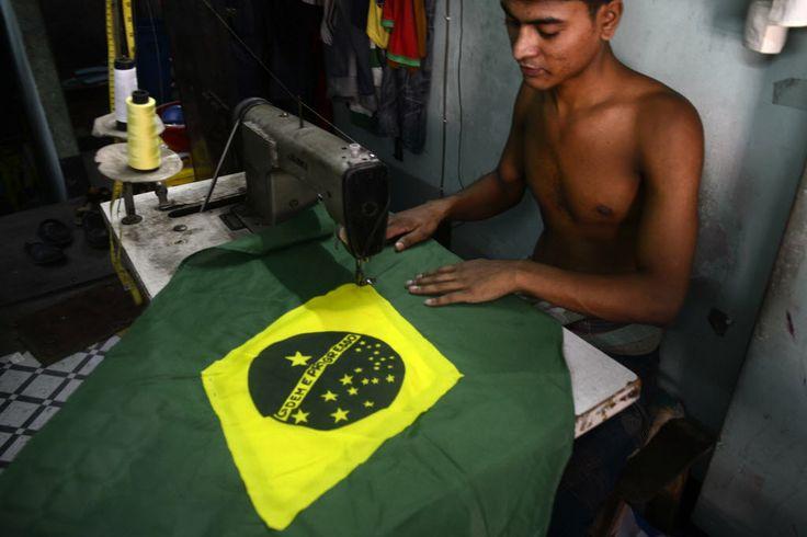 Trabalhador costura uma bandeira nacional brasileira para ser vendida antes do Mundial de Futebol da FIFA, em Dhaka, Bangladesh. Foto: Munir Uz Zaman/AFP