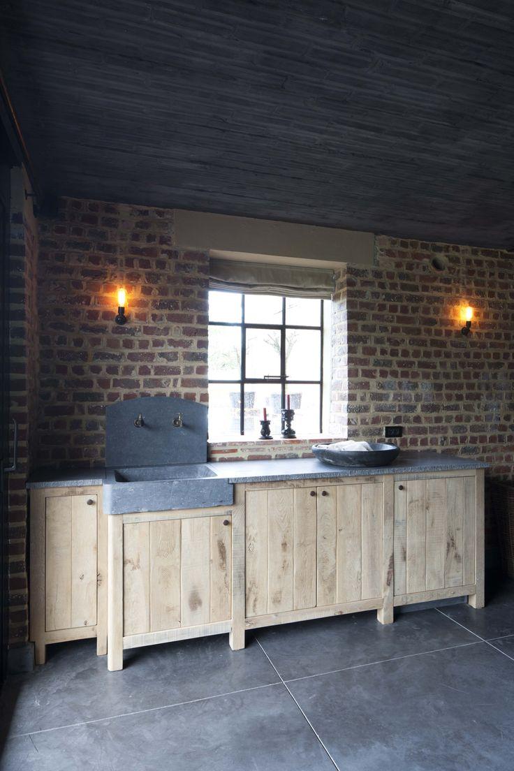 keukenblok met oude spoelbak in blauwe hardsteen op maatwerk van geloogde eiken kasten een project van DIRK COUSAERT