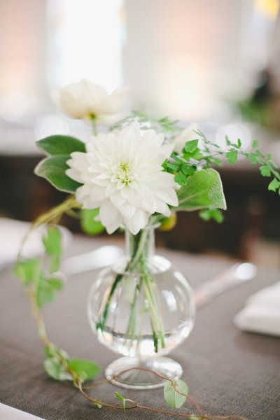 Assorted white flowers in small vases with lots of greenery- love the vines!