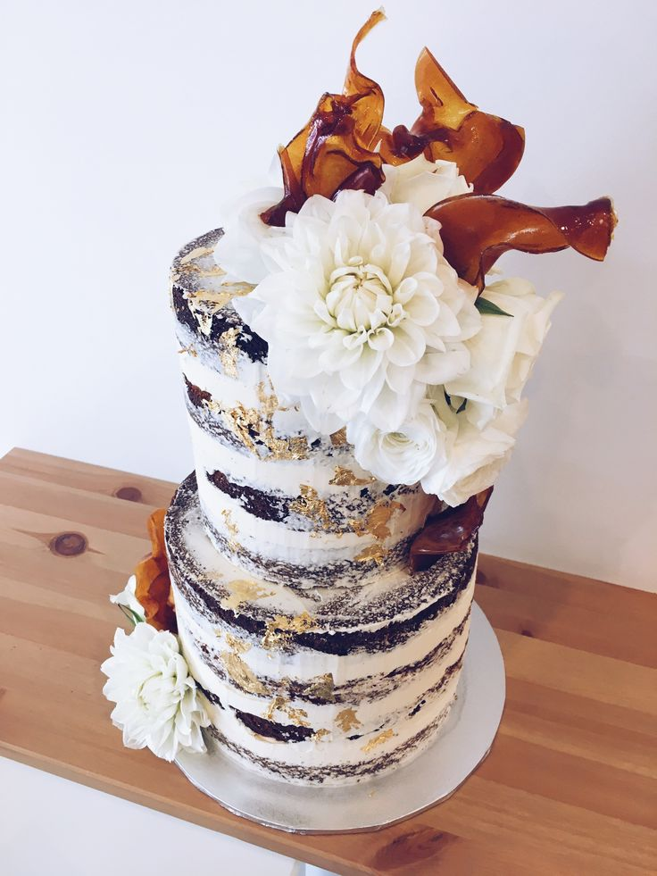 White naked buttercream wedding cake with gold leaf specks, white blooms dahlia & flame like toffee shards to add a unique touch #haranspatisserie