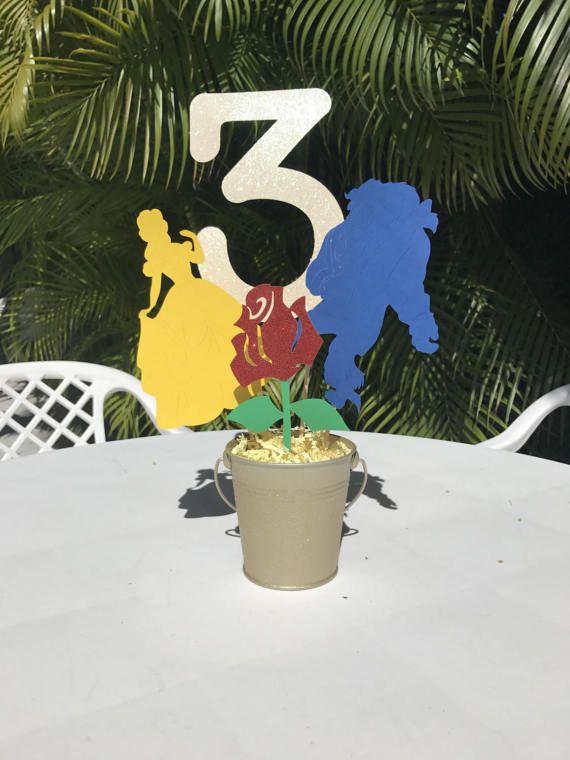 Esta hermosa belleza y la bestia inspirado centro de mesa es perfecto para los más pequeños la fiesta de cumpleaños!   Este artículo se hace con tarjeta de papel stock, papel stock de la tarjeta de brillo, taburetes de madera y un cubo de metal.  Dimensiones de la pieza central: Cubo: 4,5 pulgadas de alto Belle: 7 pulgadas de alto Bestia: 7 pulgadas de alto Flor: 6 pulgadas de alto #: 8,5 pulgadas de alto  Centro de mesa montado: aprox. 16,5 pulgadas de alto  En las notas de la sección d...
