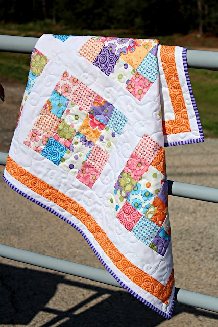 love everything about this - the orange accent border, the bias striped binding, the modern scraps and especially the swirly quilting! ...oh and that it's displayed over a farm GATE ;)