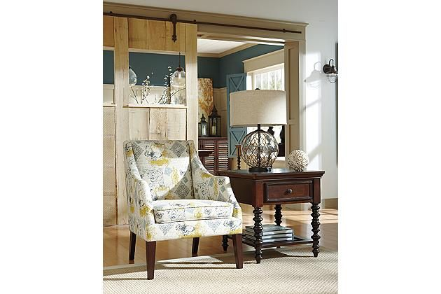 Brown wooden legs with a white, yellow, and blue patterned fabric for this accent chair