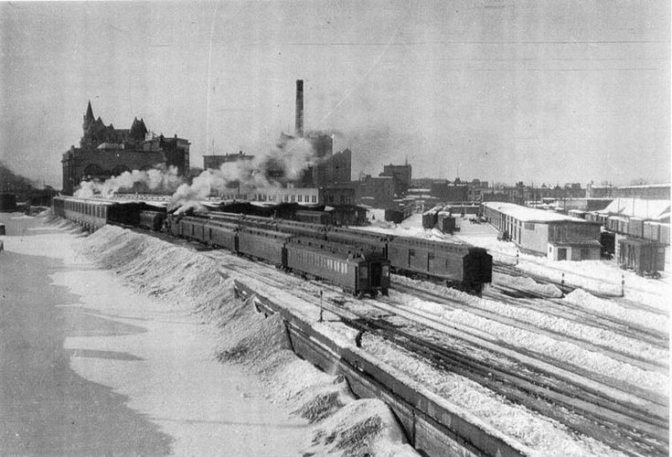 A very old picture of Ottawa Union from the Laurier Avenue bridge looking westward towards the Chateau Laurier with the winter snows from the station grounds pushed into the Rideau Canal. Freight shed at right.
