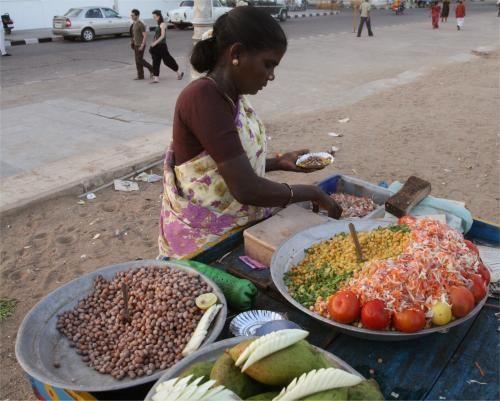 Petite collation sur le front de mer de Pondichéry (Tamil Nadu) En fin d'après-midi à Pondichéry, la chose à faire est de se balader le long du bord de mer, en profitant des brises marines... Et en vous laissant tenter par les étranges petites assiettes proposées par cette dame.