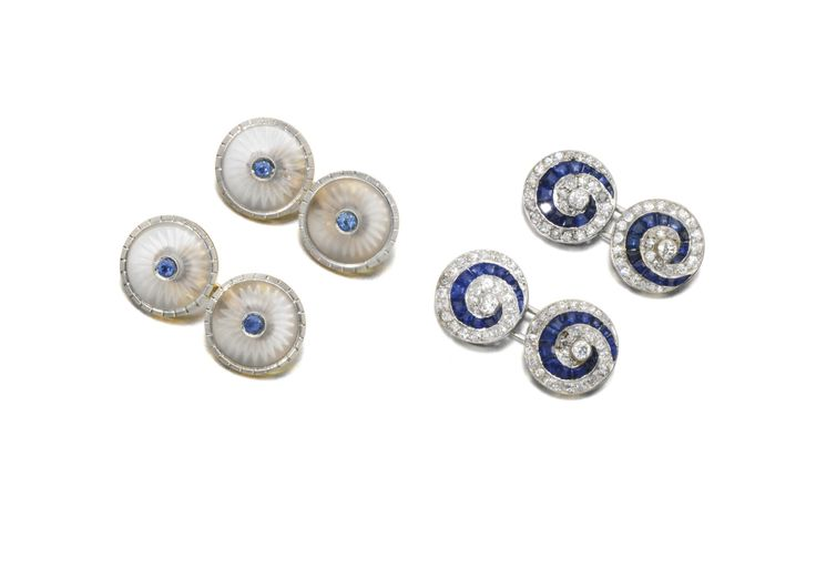 TWO PAIRS OF SAPPHIRE CUFFLINKS Comprising: a pair designed as carved rock-crystal discs inset with a circular-cut sapphire, 1920s; and a pair of whirl design, set with lines of calibré-cut sapphires, circular- and single-cut diamonds.