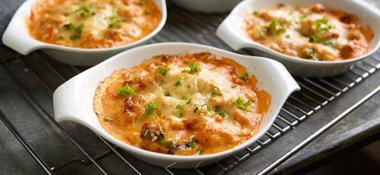 Meng de vissoep met de room en laat op een matig vuur 10 min. inkoken tot een dikke saus. Bak de groenteblokjes samen met de geperste look 5 min. in de boter. Doe de blokjes vis bij de groenten, samen met het mosselvlees, de inktvisringen en garnalen. Kruid met peper en zout. Verdeel over meerdere vuurvaste ovenschoteltjes en overgiet met de saus. Zet 15 min. in een warme oven, stand 6 (180°C). Bestrooi 5 min. voor het einde van de baktijd met kaas. Versier met sprietjes dille en dien met...